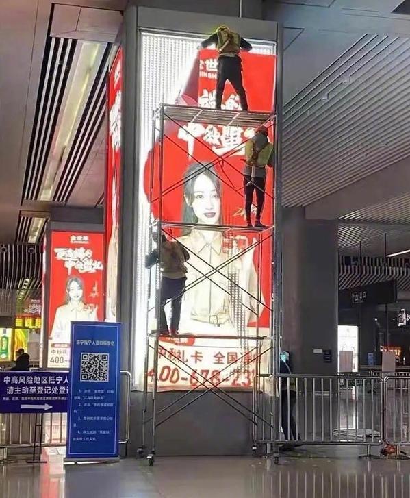 Công nhân gỡ ảnh quảng cáo của Trịnh Sảng trong đêm, tại một ga tàu cao tốc ở Trung Quốc. Ảnh: Sohu.