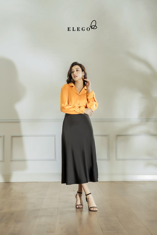 Áo sơ mi cam phối chân váy dài midi là item được nhiều quý cô ưa chuộng khi đến Elego. Chất liệu lụa phù hợp với tiết trời nóng bức mùa hè nhưng vẫn đảm bảo kín đáo, thanh lịch nơi công sở.