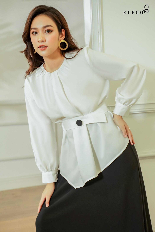 Đen, trắng là màu sắc không thể thiếu trong tủ đồ phái nữ. Áo cổ tròn cách điệu, lạ mắt với chi tiết xếp ly cùng thân áo xéo tà, phối ăn ý cùng chân váy đen.