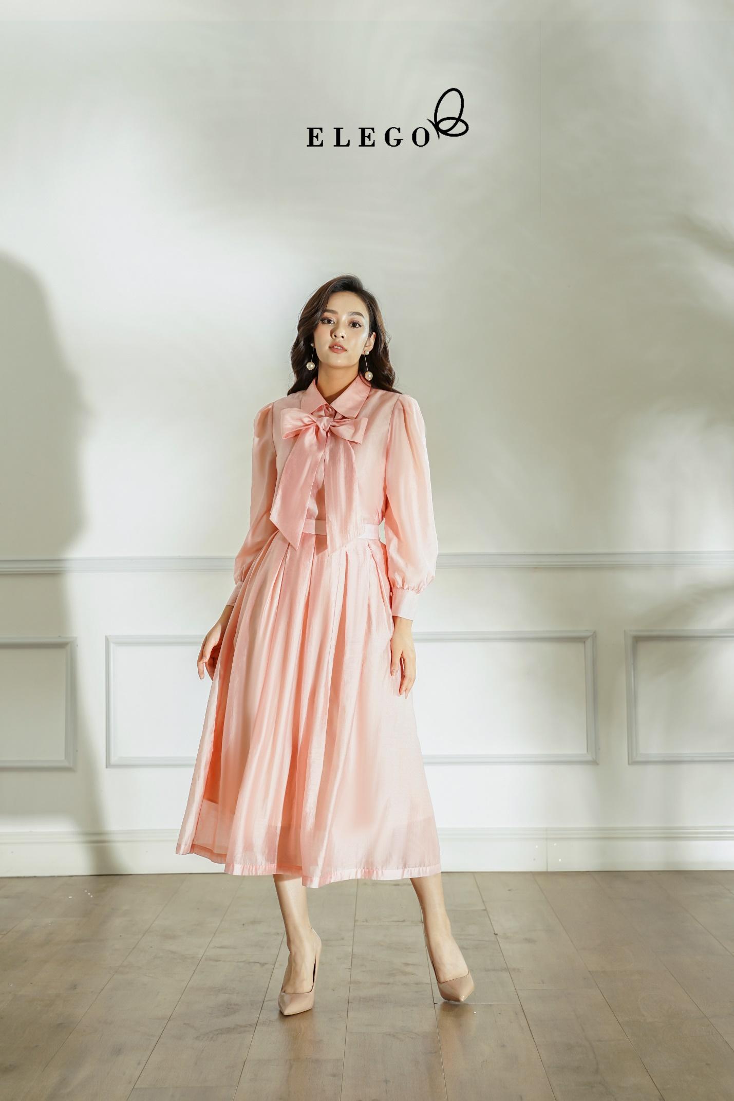 Các cô ái yêu thích lãng mạn có thể chọn áo tơ hồng thắt nơ và chân váy xếp ly cùng màu bồng bềnh. Set đồ của Elego hợp với nơi công sở, bữa tiệc hay dạo phố.