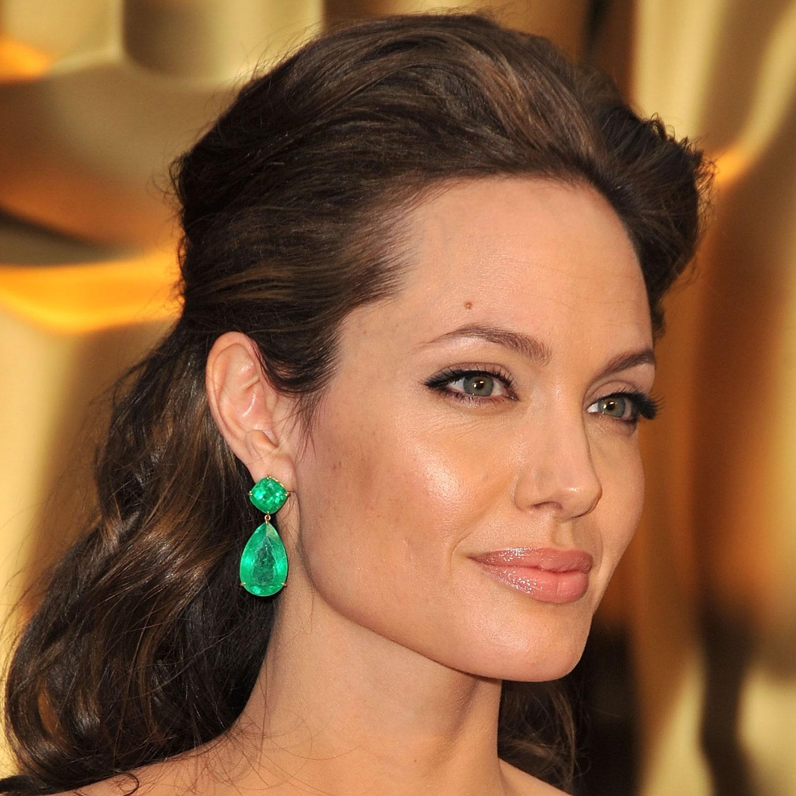 Phong cách thoa son bóng màu nude cũng được Angelina Jolie áp dụng năm 2009 với tông trang điểm tự nhiên, chỉ kẻ chút eyeliner cho đôi mắt thêm sắc sảo. Nhà tạo mẫu tóc David Babaii tạo kiểu tóc uốn sóng nhẹ cho nữ diễn viên, phần tóc hai bên buộc gọn phía sau, tôn lên gương mặt cùng khuyên tai ngọc lục bảo. Ảnh: Allure.