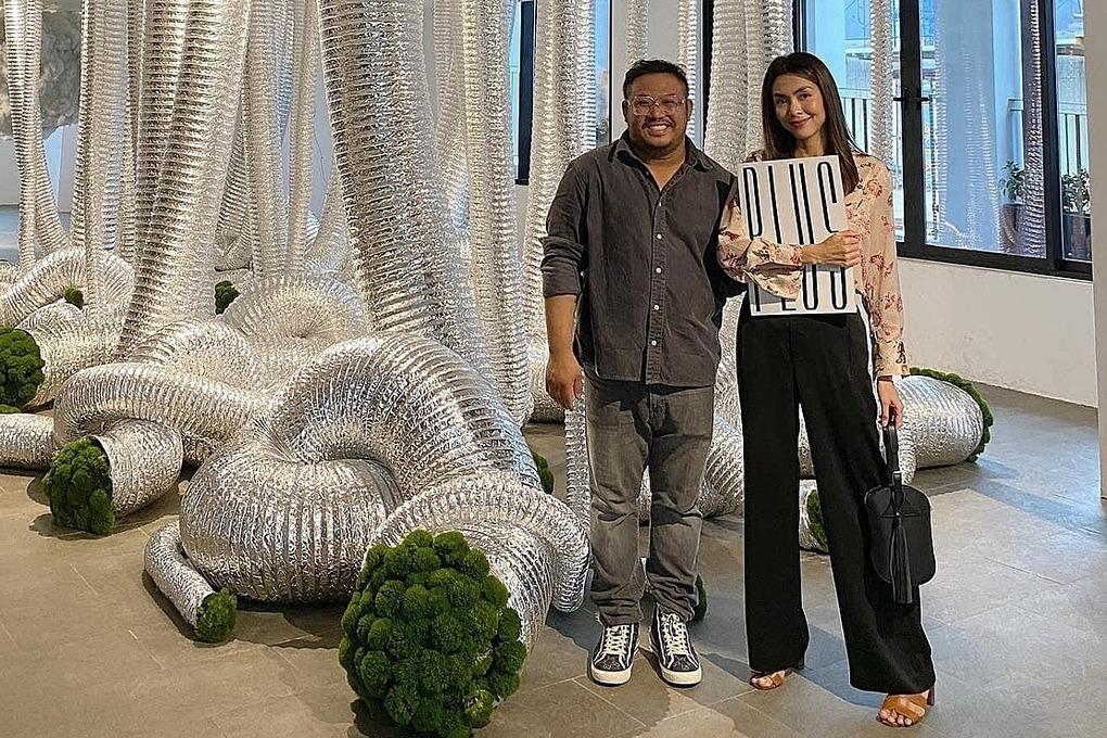 Tăng Thanh Hà và Bảo Nam (trái) bên tác phẩm hoa trong ống dẫn gas. Cô đi xem triển lãm trưa 10/4. Ảnh: Dung Cao.