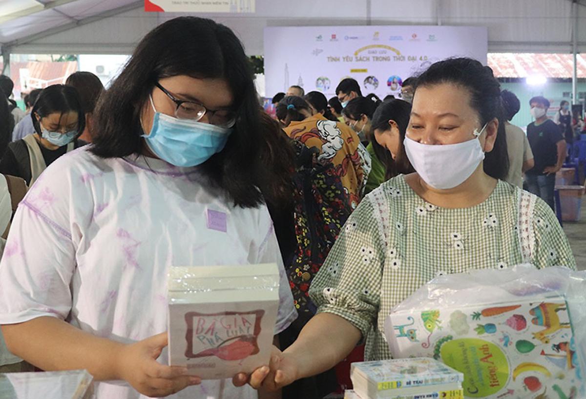 Chị Nguyễn Ngọc Thanh Hà (bên phải) cùng con đi mua sách. Ảnh: Thanh Tuyền.