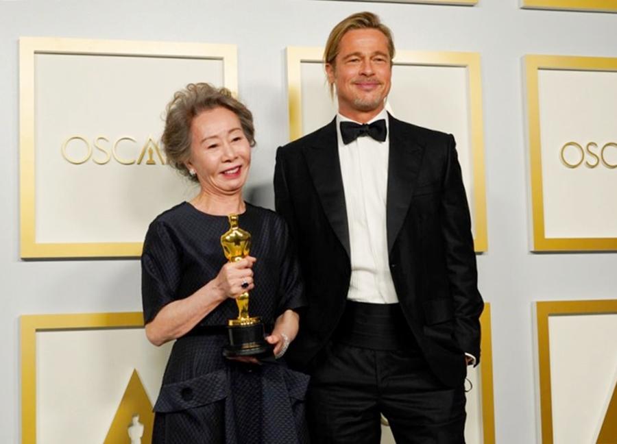 Youn Yuh Jung chụp hình cùng Brad Pitt sau khi nhận tượng vàng. Ảnh: AP.