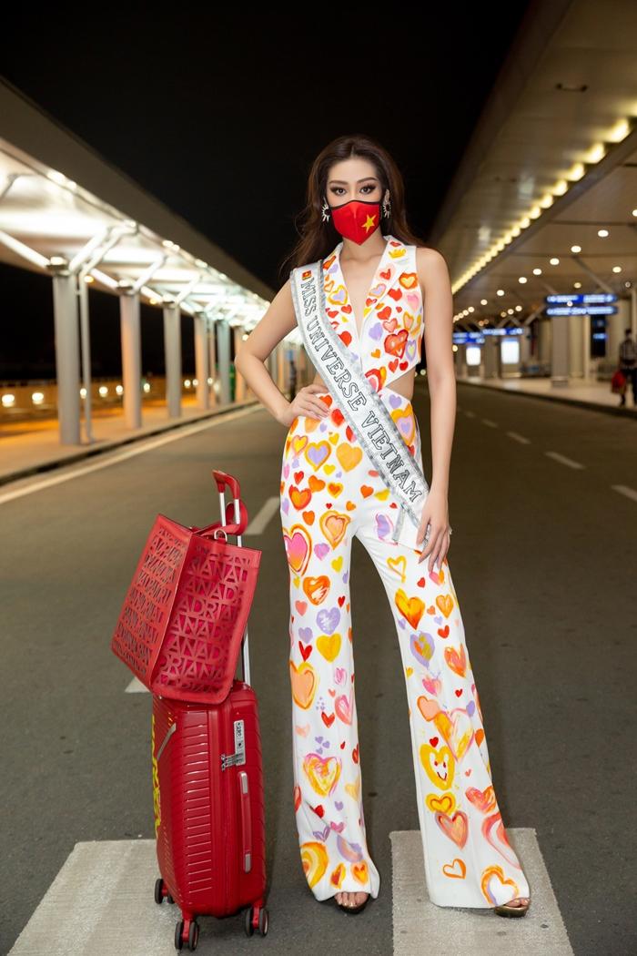 Tại sân bay Tân Sơn Nhất, hoa hậu khởi hành với bộ jumpsuit khoét eo, họa tiết trái tim do các thành viên trong êkíp, người hâm mộ của cô vẽ tặng, gởi gắm tình yêu và lời chúc may mắn.