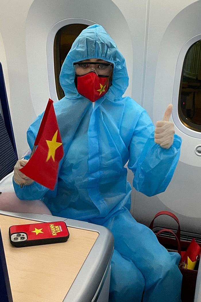 Suốt chặng bay, Khánh Vân luôn mặc trang phục bảo hộ. Khẩu trang và vỏ điện thoại đỏ in sao vàng của cô cũng được thiết kế riêng cho chuyến đi.