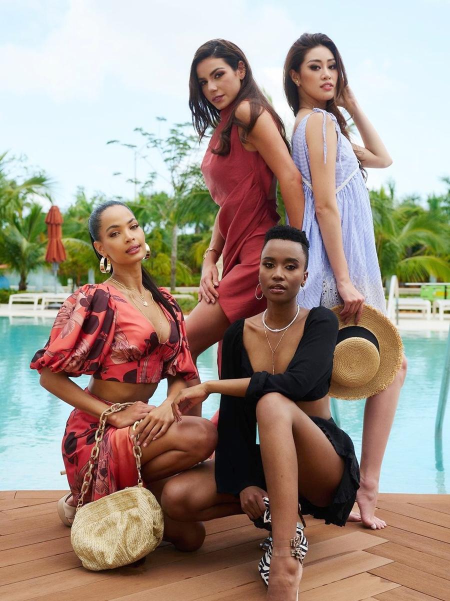 Ban tổ chức Miss Universe vừa đăng tải loạt ảnh các thí sinh tại bể bơi - thuộc khuôn viên khách sạn nơi các người đẹp lưu trú - trong hoạt động chụp hình hôm 7/5. Khánh Vân (váy xanh) đọ dáng bên Miss Universe 2019 - Zozibini Tunzi (váy đen), người đẹp Brazil - Julia Gama (đứng) đại diện Cộng hòa Dominican - Kimberly Jiménez.