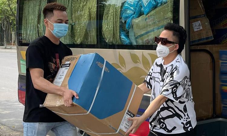 Tùng Dương (phải) và trợ lý sắp xếp vật phẩm ủng hộ trưa ngày 19/5. Ảnh: Nhân vật cung cấp.