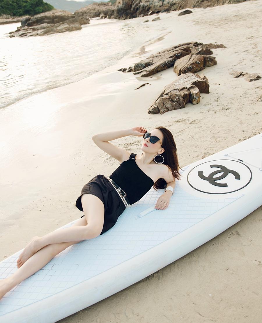 Người đẹp phối quần short, áo lệch vai cùng dây lưng Chanel khi đi chơi biển.