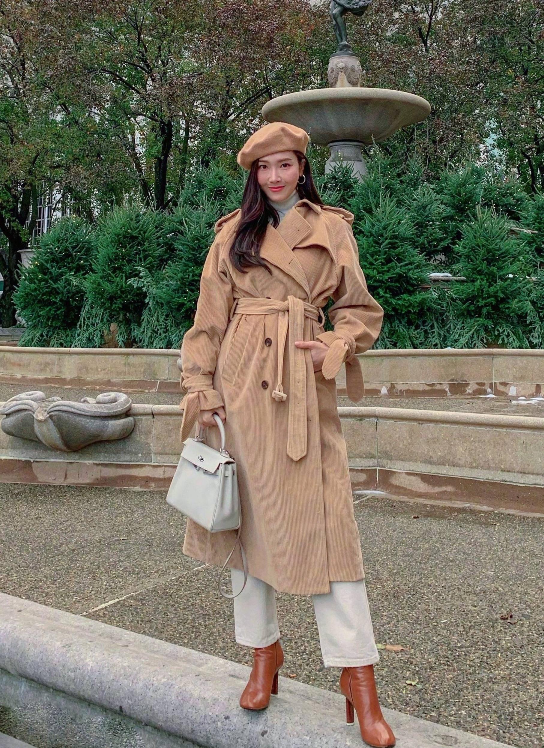 Thần tượng Hàn Quốc ghi điểm với set đồ phong cách cổ điển, sang trọng gồm: mũ beret, quần kaki, trench coat màu camel (vàng lạc đà) và boots da. Cô mang túi Hermes dòng Kelly, size 28 cm, giá 12.130 USD.
