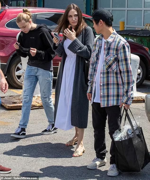 Ngày khác, cũng với chiếc áo này, Pax làm thành áo khoác khi mặc cùng áo phông trắng khi đi cùng mẹ và em gái. Ảnh: Splash News.