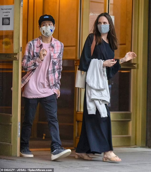 Cũng trong tháng này, họ đến căn hộ của chồng cũ Jolie - Jonny Lee Miller. Trong khi Jolie mặc váy maxi đen, Pax phối sơ mi kẻ cùng tông với áo phông hồng. Ảnh: Splash News.