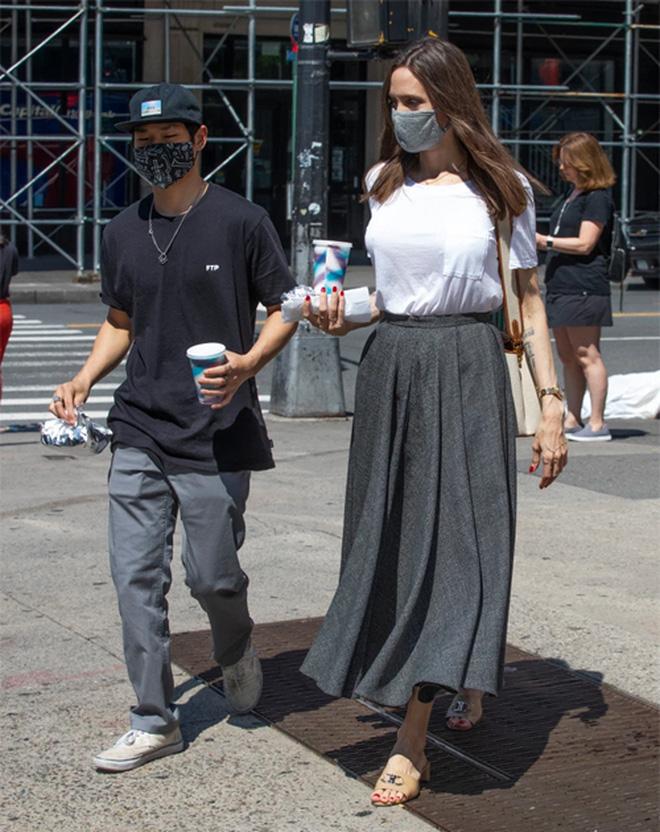 Angelina Jolie cùng Pax Thiên và Knox ghé vào cửa hàng bán bánh mì kẹp xúc xích nổi tiếng trong khi đi dạo ở New York hồi tháng 6. Pax và Jolie cùng chọn trang phục màu xám đơn giản, phong rộng vừa phải để tiện cho các hoạt động ngoài trời. Ảnh: Splash News.