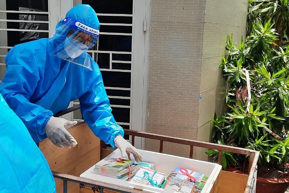 Các tình nguyện viên mang sách đến một khu phong tỏa trong hẻm. Ảnh: NXB Tổng hợp TP HCM.