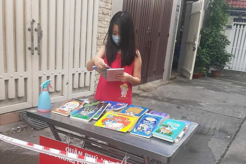 Một độc giả nhí ở phường 8, quận Phú Nhuận lựa truyện trên bàn sách ở khu phong tỏa. Ảnh: NXB Tổng hợp TP HCM.