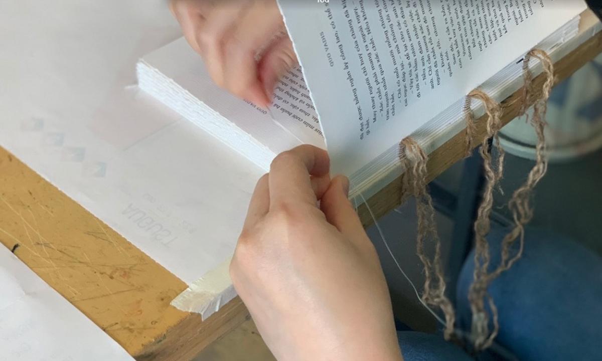 Thợ thủ công khâu sách Bố già bằng kỹ thuật khâu rết cổ điển. Ảnh: Đông A.