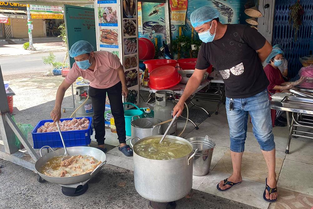 Nhóm bếp của nghệ sĩ Hữu Quốc chuẩn bị các suất ăn cho người nghèo. Ảnh: Vũ Trần.