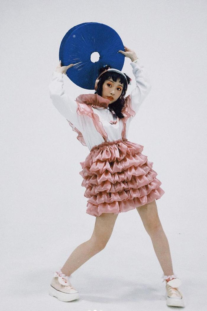 Ca sĩ chụp ảnh thời trang với váy xếp tầng gam hồng, trắng phong cách tinh nghịch.
