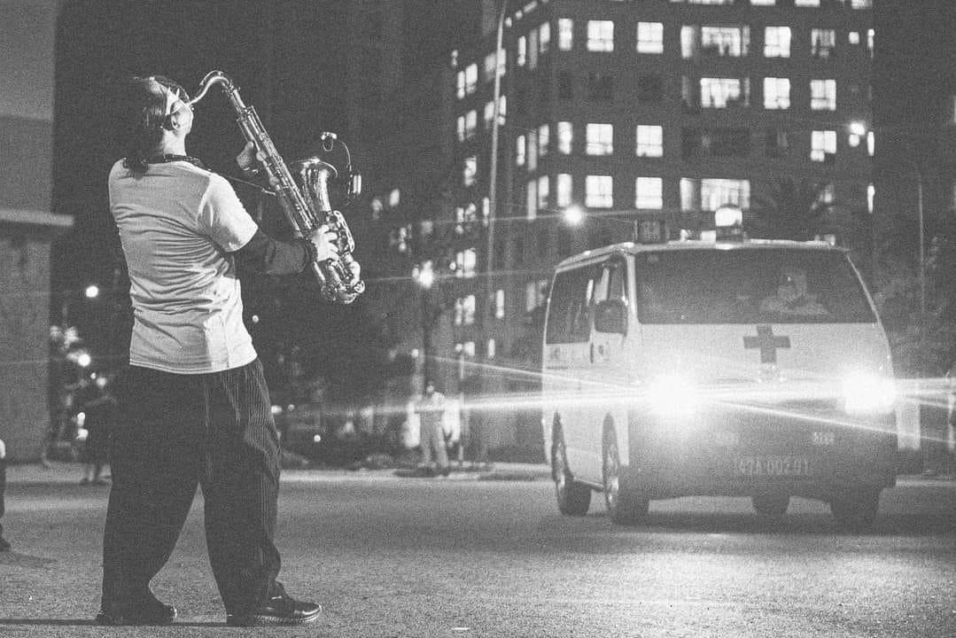 Hình ảnh nghệ sĩ Trần Mạnh Tuấn thổi saxophone tại sân bệnh viện dã chiến TP HCM tối 24/7 gây sốt trên mạng xã hội. Anh cho biết đây là sân khấu đặc biệt nhất trong cuộc đời mình, với 10.000 khán giả là bệnh nhân F0 và y bác sĩ, nhân viên y tế. Chiếc khẩu trang của anh được khoét một lỗ vừa đủ để thổi kèn. Nhiều người đã rơi nước mắt khi những giai điệu của ca khúc Quê hương (nhạc Giáp Văn Thạch, thơ Đỗ Trung Quân) vang lên. Ảnh: Quỷ Cốc Tử.