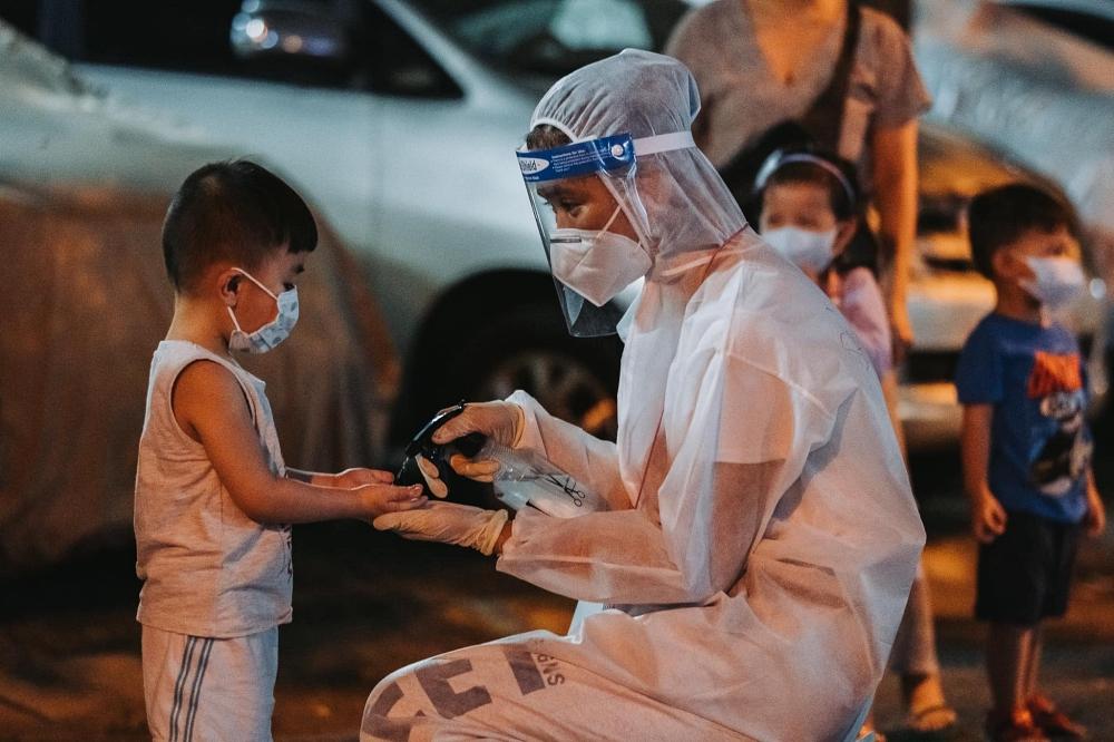 Á hậu Mâu Thủy phun nước rửa tay cho một em bé trước khi vào xét nghiệm Covid-19. Người đẹp tham gia làm tình nguyện viên hỗ trợ tuyến đầu chống dịch từ những ngày đầu tiên. Ảnh: Neih Nguyen.