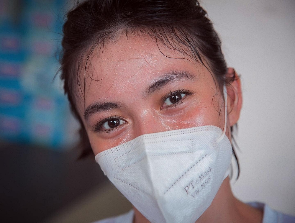 Làm việc dưới thời tiết nắng nóng, gương mặt cô đỏ bừng, in hằn dấu khẩu trang. Mâu Thủy cho biết cô sẽ không dừng lại cho đến khi nào TP HCM kiểm soát được dịch.  Ảnh: Neih Nguyen.