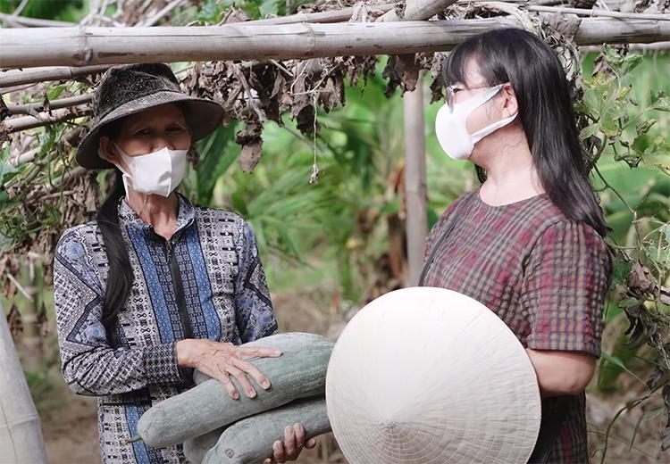 Ánh Tuyết (phải) bên một người dân thu hoạch nông sản gửi vào Nam. Ảnh: Trí Lê.