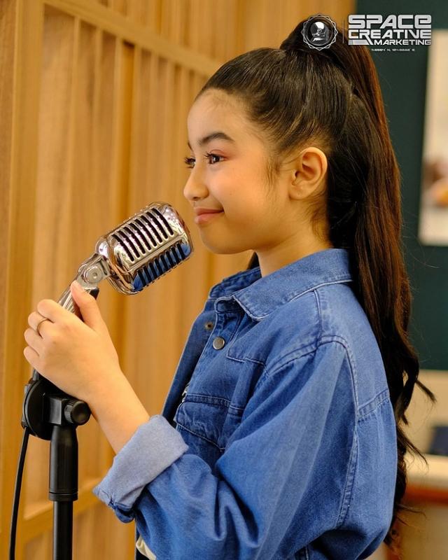 Áo khoác denim và kiểu tóc cột cao giúp cô bé trông năng động, tinh nghịch khi đi thu âm.