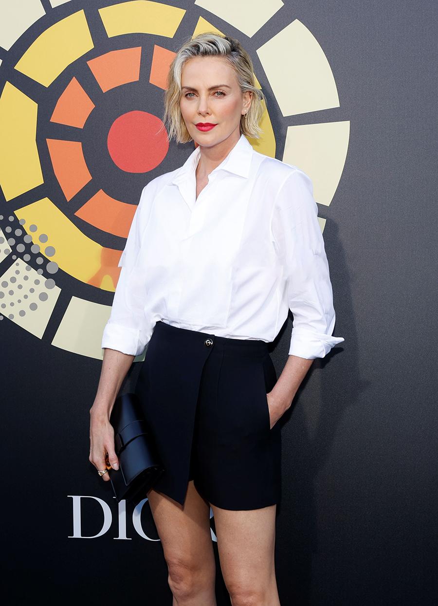 Charlize Theron chọn sơ mi trắng, chân váy đen của Dior phối túi Montaigne 30 và hoa tai Melinda Maria khi tham gia sự kiện CTAOPs Night Out 2021: Fast And Furious ở California, hôm 28/6. Ảnh: Reuters.
