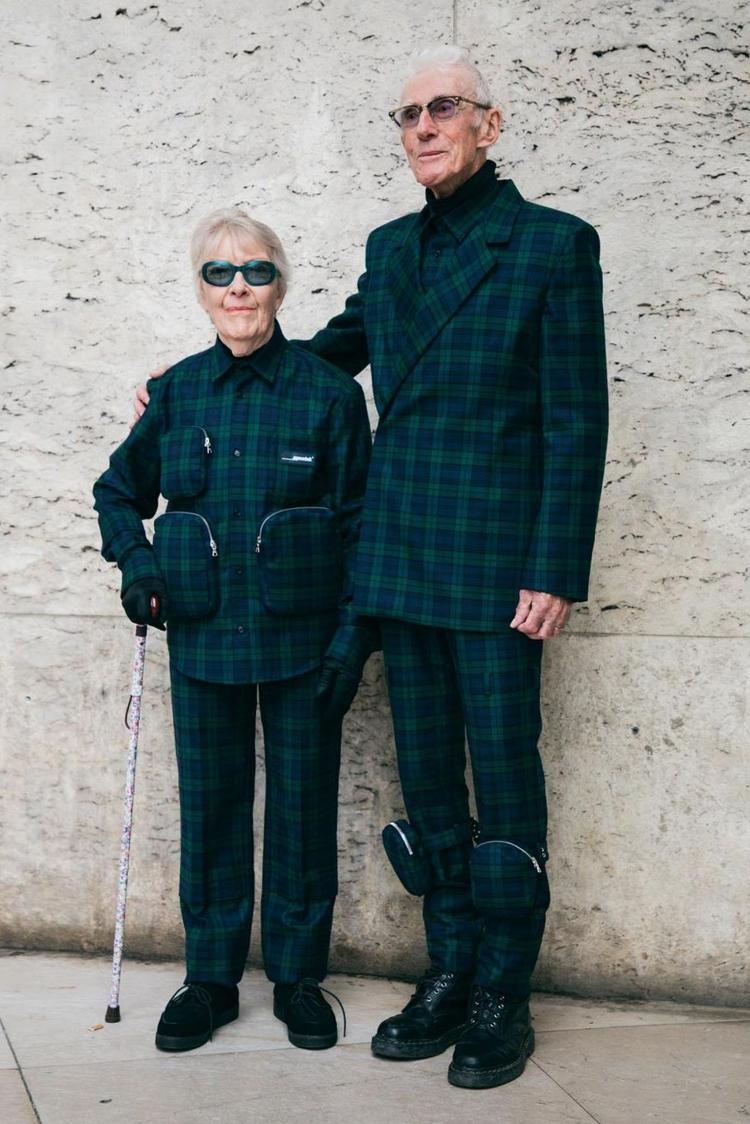 Hai ông bà diện trang phục hoạ tiết caro xanh đậm. Trang phục vẫn mang phong cách unisex đặc trưng của EgonLab nhưng kết hợp thêm chi tiết túi khoá kéo may nổi bên trên bề mặt vải để tạo điểm nhấn.