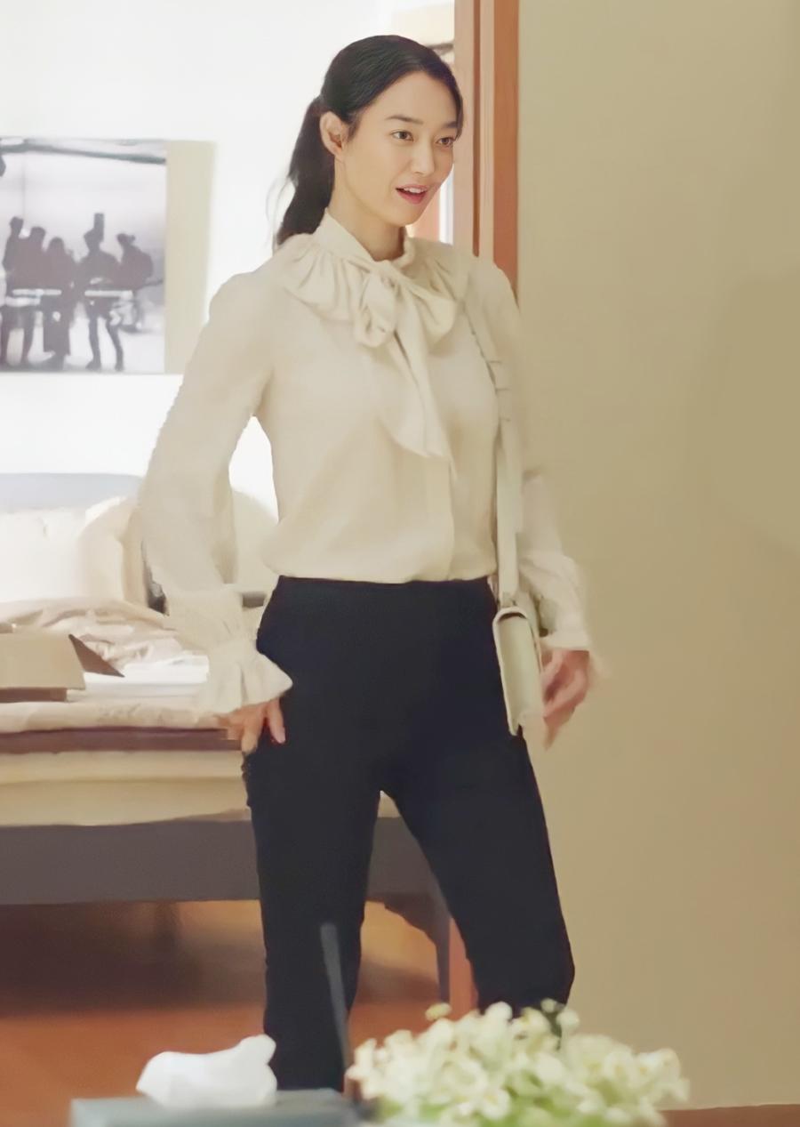 Trước đó, trong cảnh chọn đồ, cô mặc sơ mi thắt nơ giá 1.390 USD (31 triệu đồng) và túi xách giá 2.900 USD (66 triệu đồng) của nhà mốt Saint Laurent.