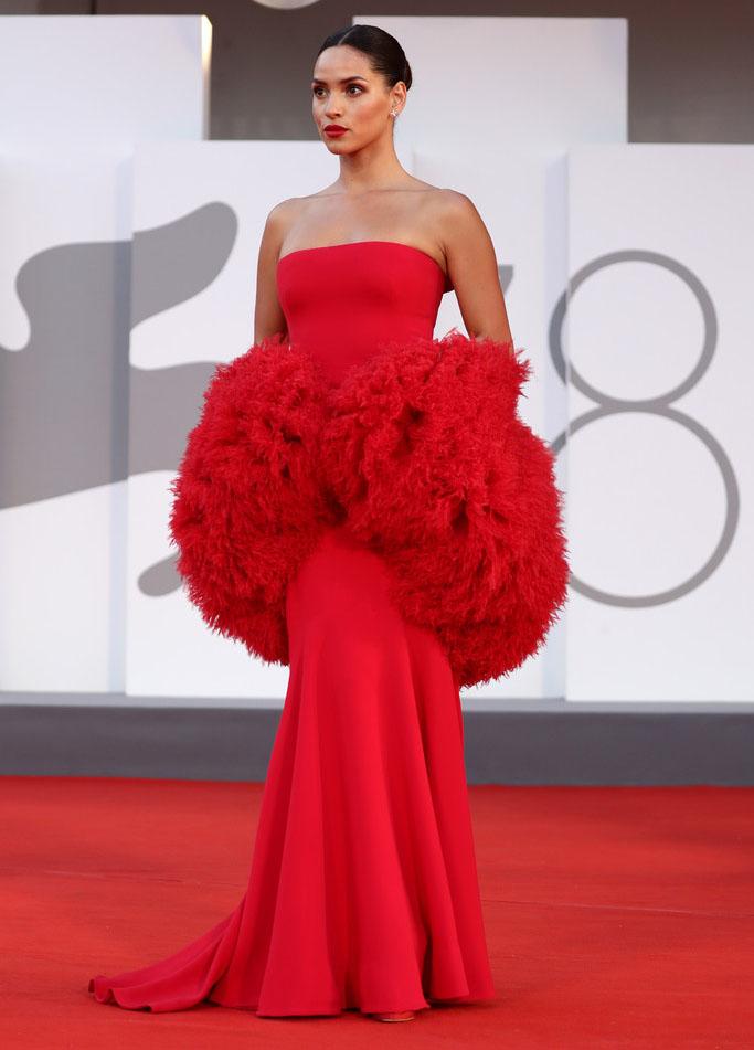 Liên hoan phim Venice lần thứ 78 diễn ra ở đảo Lido từ ngày 1 đến 11/9, quy tụ nhiều ngôi sao trong lĩnh vực điện ảnh, thời trang thế giới. Thảm đỏ năm nay chứng kiến sự xuất hiện ồ ạt của các thiết kế đến từ nhà mốt cao cấp của Italy - Armani. Ở buổi công chiếu Last Night In Soho, diễn viên Adria Arjona nổi bật trong bộ đầm đỏ quây ngực của Armani với phần hông tạo khối 3D, thuộc bộ sưu tập Haute Couture Thu Đông 2014. Ảnh: Vogue