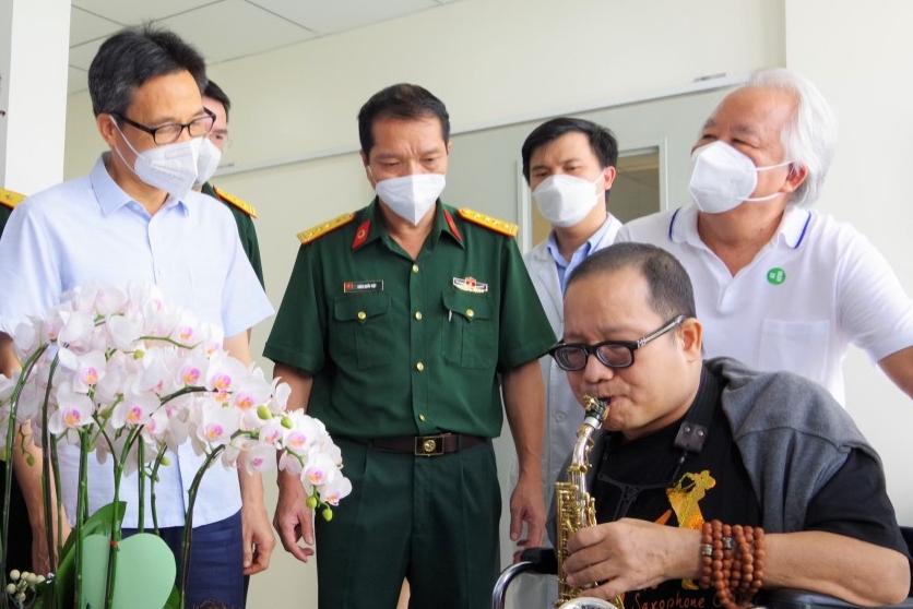 Ông Vũ Đức Đam (trái) động viên Trần Mạnh Tuấn không khóc. Ảnh: Nhân vật cung cấp